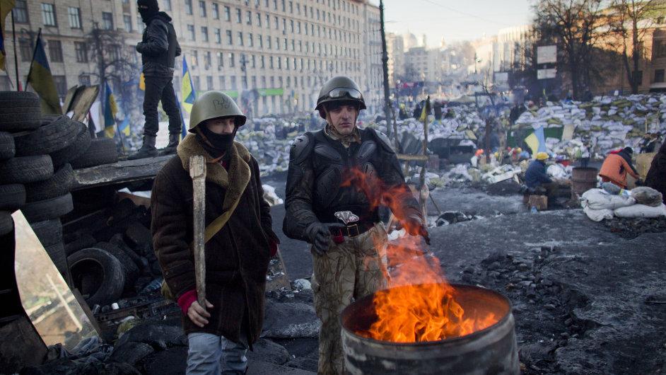Protivládní demonstranti se ohřívají v centru Kyjeva.