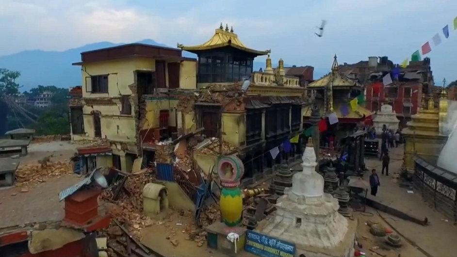 Vlajky a zkáza: Letecký snímek poničeného domu