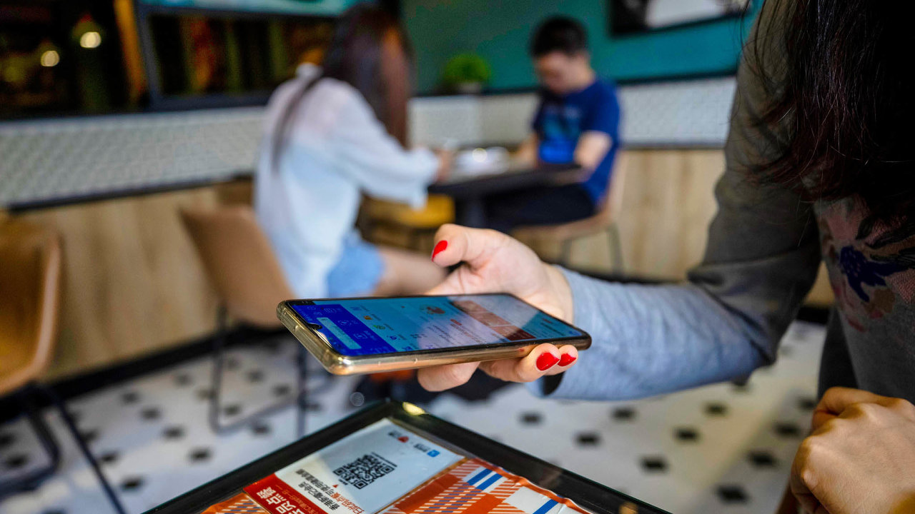 A woman uses her mobile phone to scan a code with Alipay application to view the menu and for payment