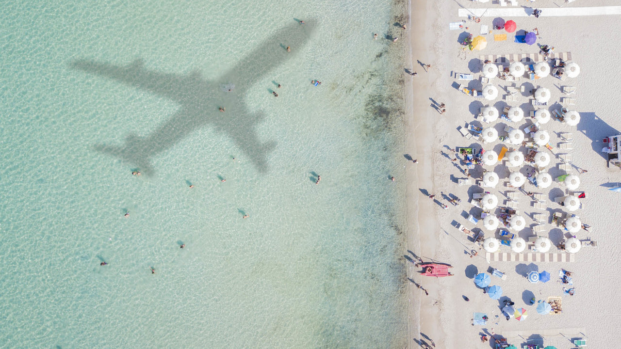 Aerial view of the amazing beach with the shadow of an airplane and people who swim.